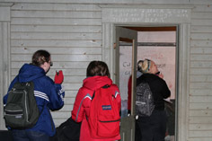 people photograhing historic graffiti in Harrington Opera House stage dressing rooms