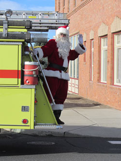 Santa waves from back of fire truck in front of Harrington Opera House